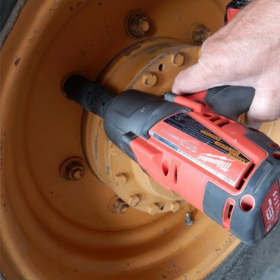 Impact wrench working on a tire with a hand