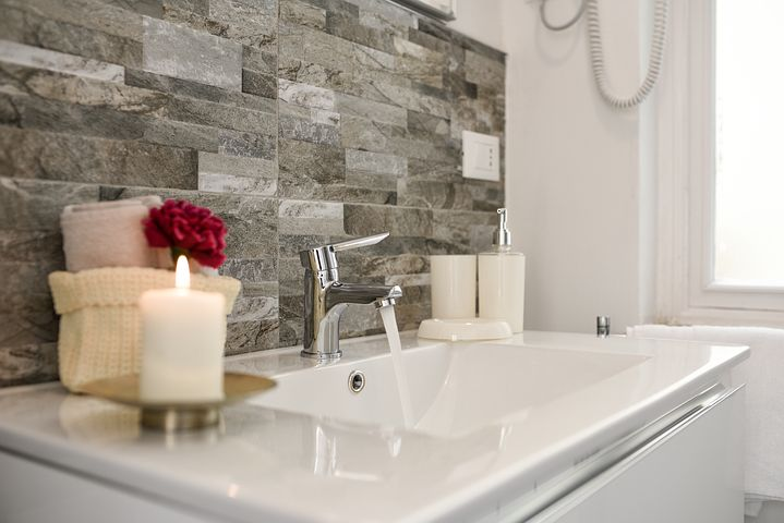Bathroom vanity with candle burning and a rose. White counter top with brick backsplash