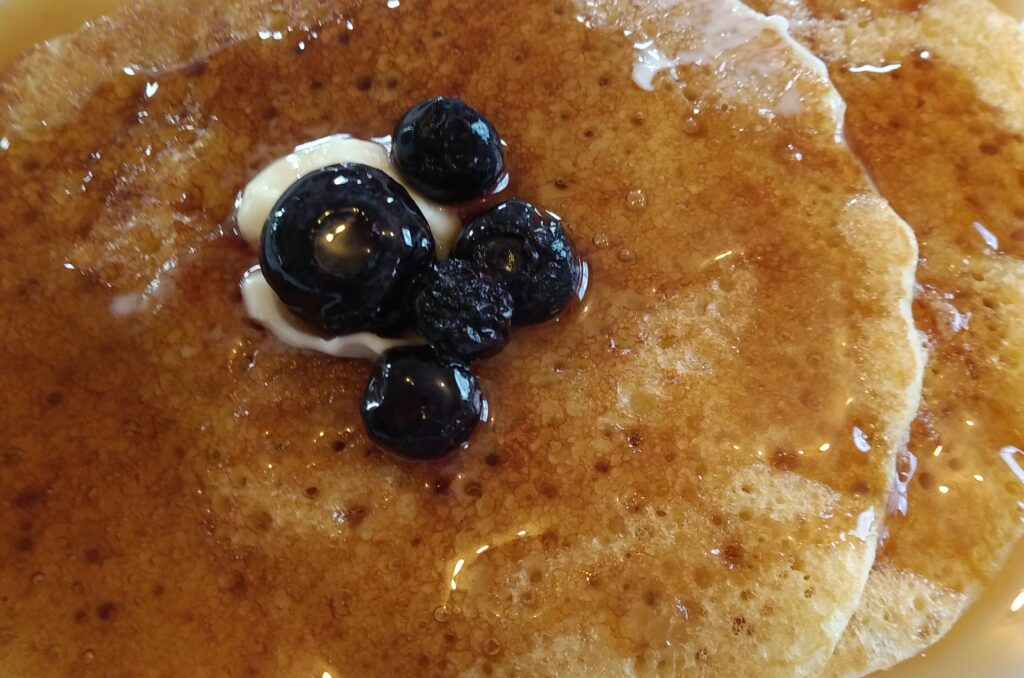 Homemade pancakes with blueberries on top with butter and syrup