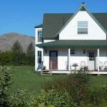 White farmhouse with a green roof, mountains in the background with green lawn, trees and shrubs