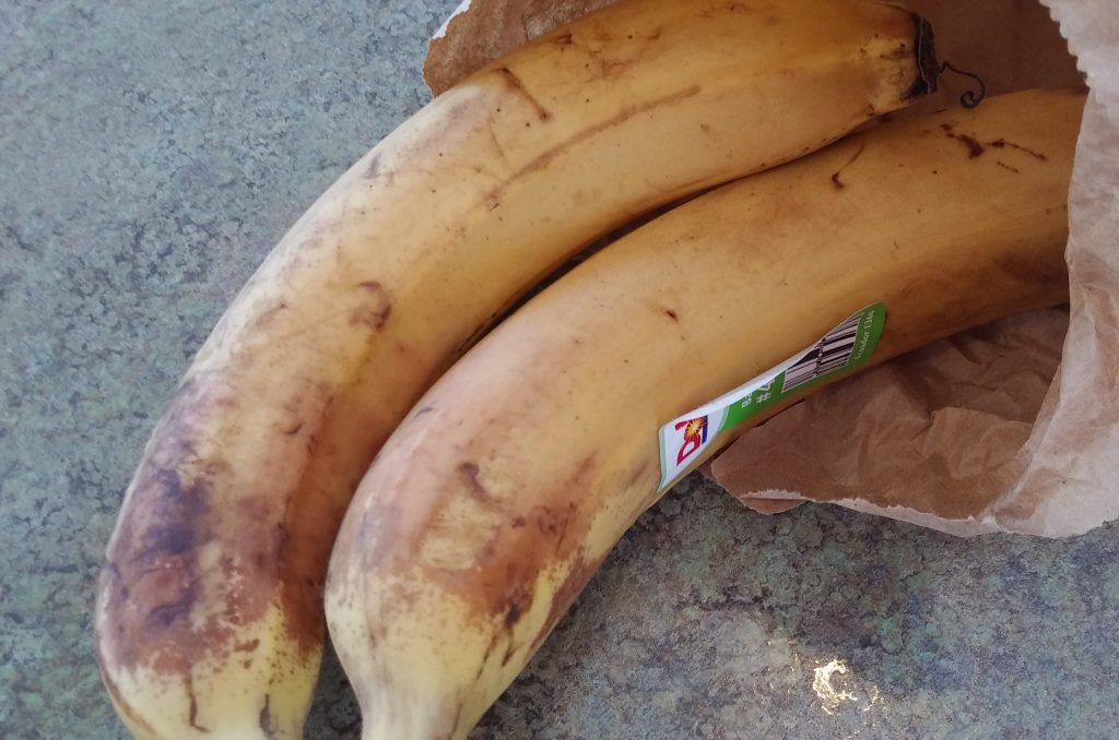 Banana with a partially brown skin hanging out of a brown paper sack