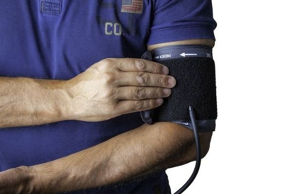Man in a blue shirt taking his blood pressure with a blood pressure cuff