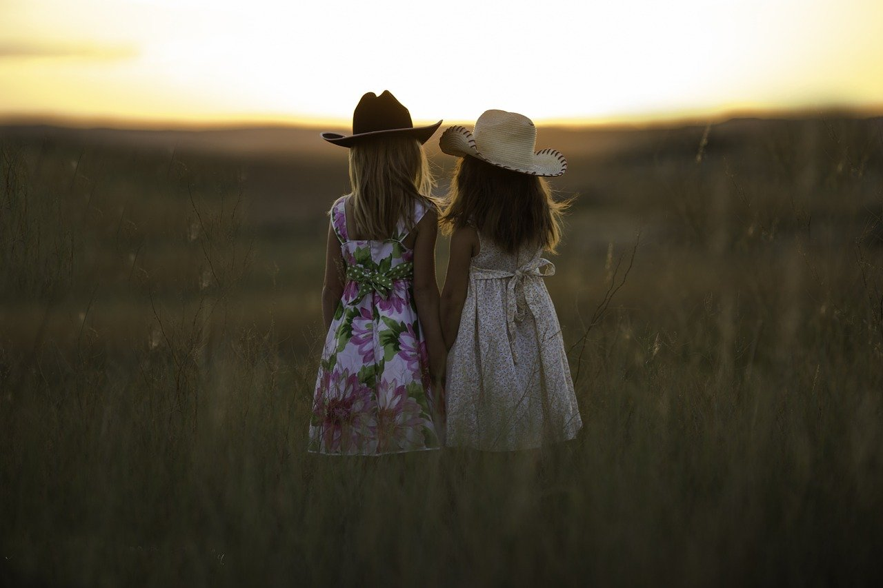 2 sisters walking through a field wearing dresses and cowboy hats holding hands.