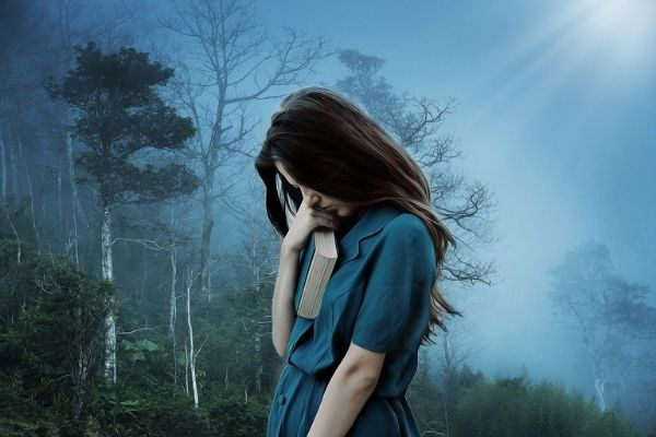 Sad girl carrying a book. Brown hair and a blue dress with a gloomy background of trees