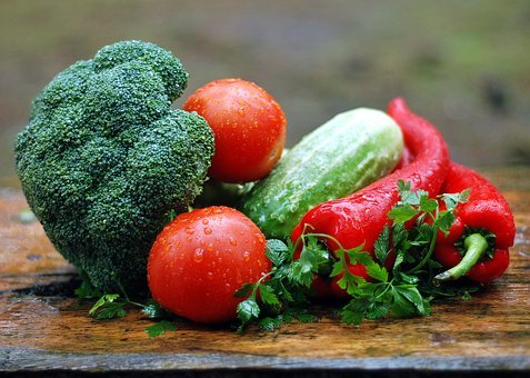 A pile of vegetables on the table. Tomatoes, cucumber, red peppers, broccoli.