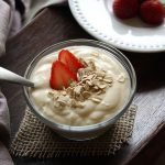 A bowl of yogurt with strawberries and oatmeal sprinkled on top.